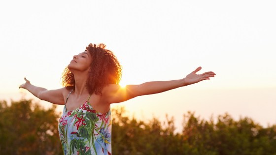 Woman with outstretched arms and eyes closed in a field at sunset