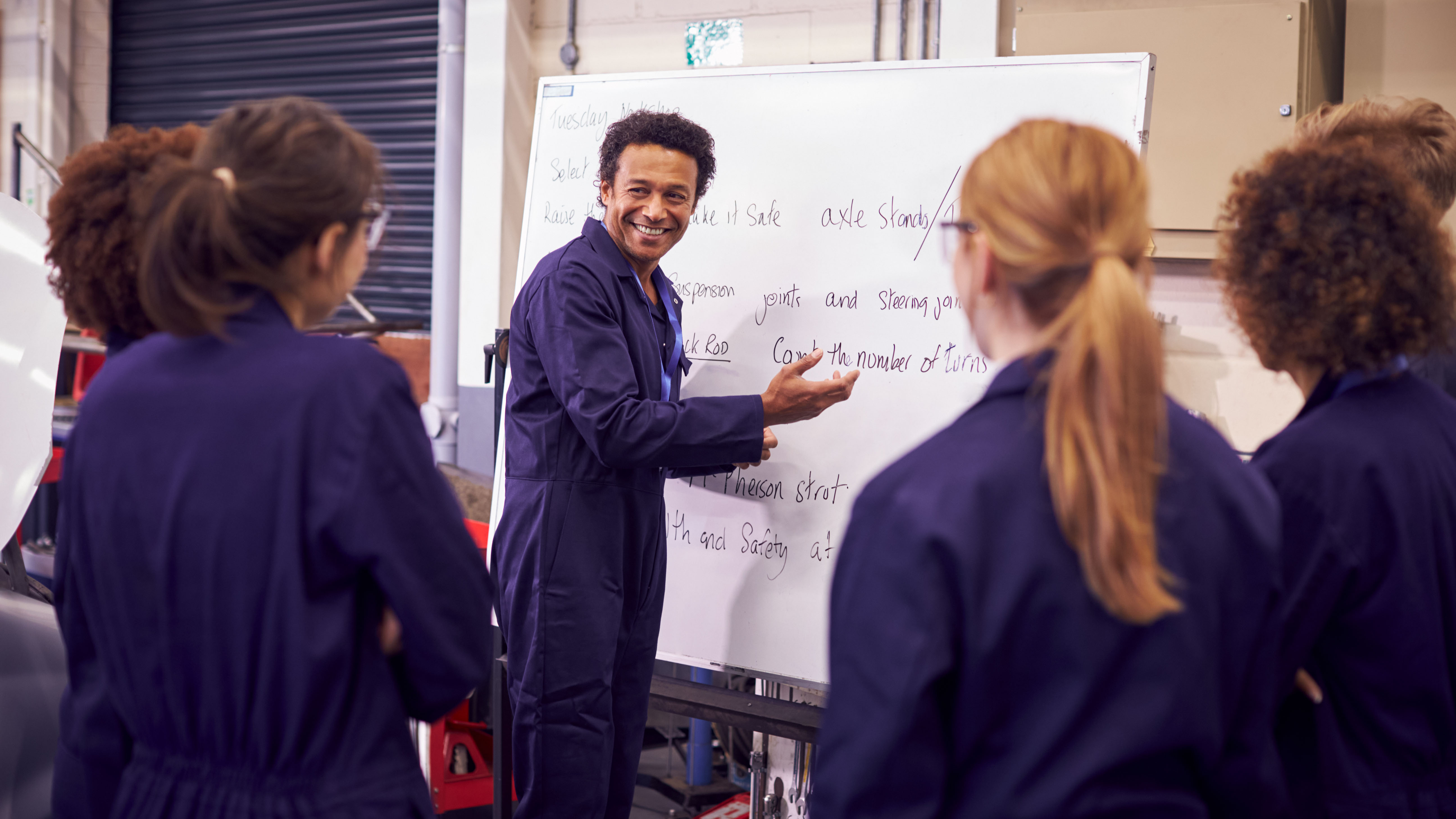 Mechanic vocational teacher in front of whiteboard in mechanic overalls surrounded by students listening