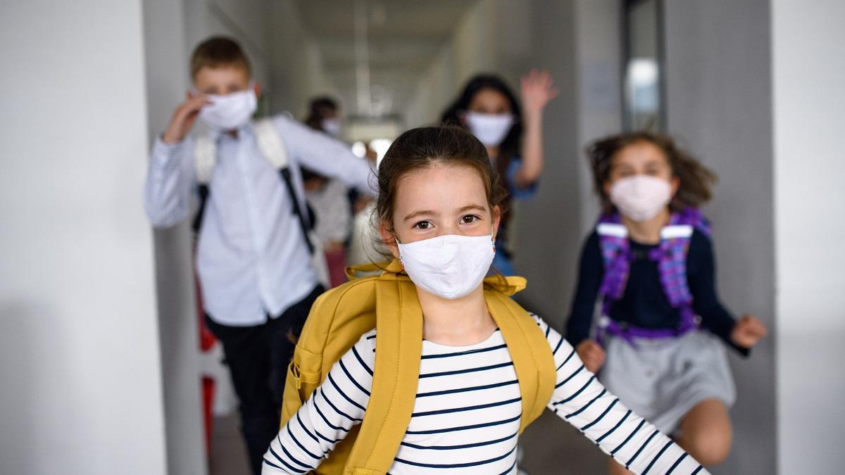 School children wearing face masks in school corridor running towards the camera