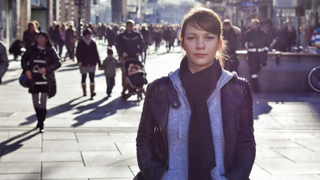 Woman looking into camera stands alone on a busy shopping street