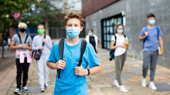 Portrait of teenager in protective covid face mask with backpack going to school lessons on sunny autumn day