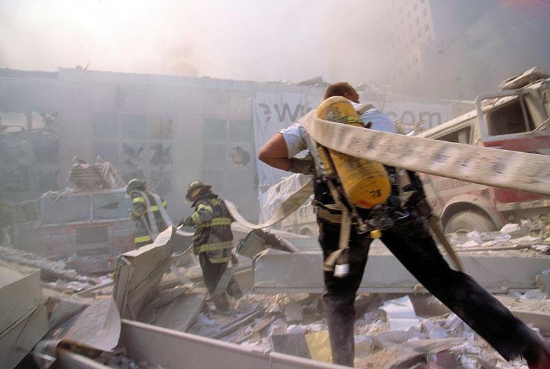Fire_fighters_carrying_water_hose_through_rubble_September_11th_following_terrorist_attack_(29138419860)