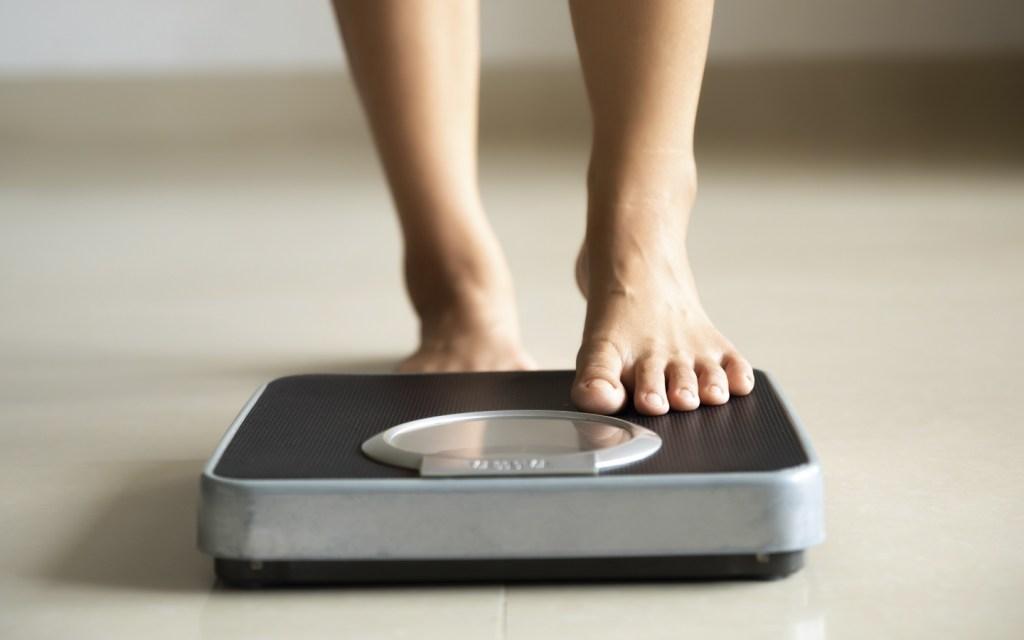 Jeune femme montant sur un balance pour prendre son poids