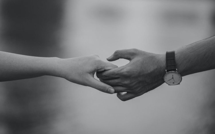 monochrome photo of couple holding hands.
