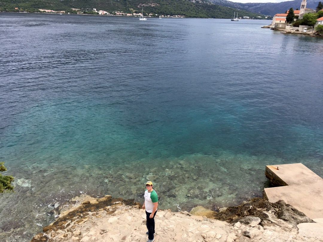 a  man stands near clear Mediterranean waters in Croatia