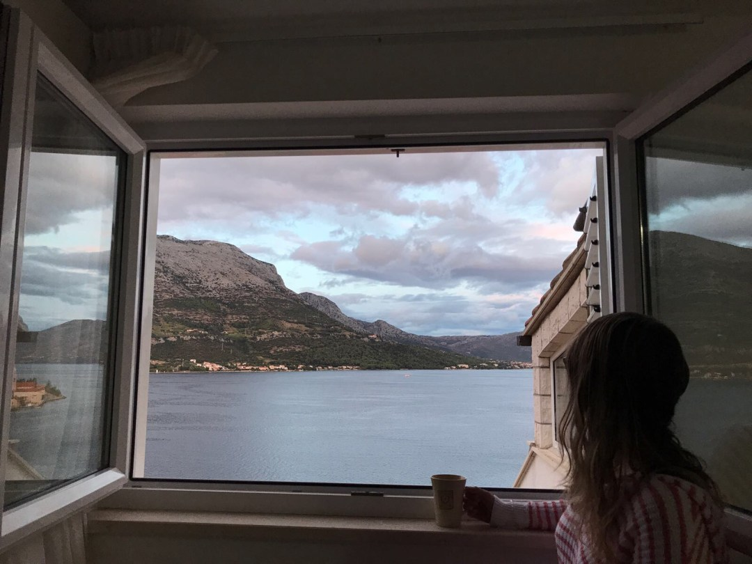 Girl looks out window at Korcula's stunning view in Croatia