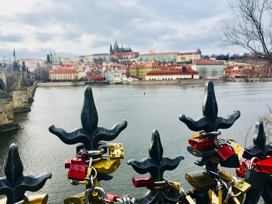 Locks on fence near river in Prague