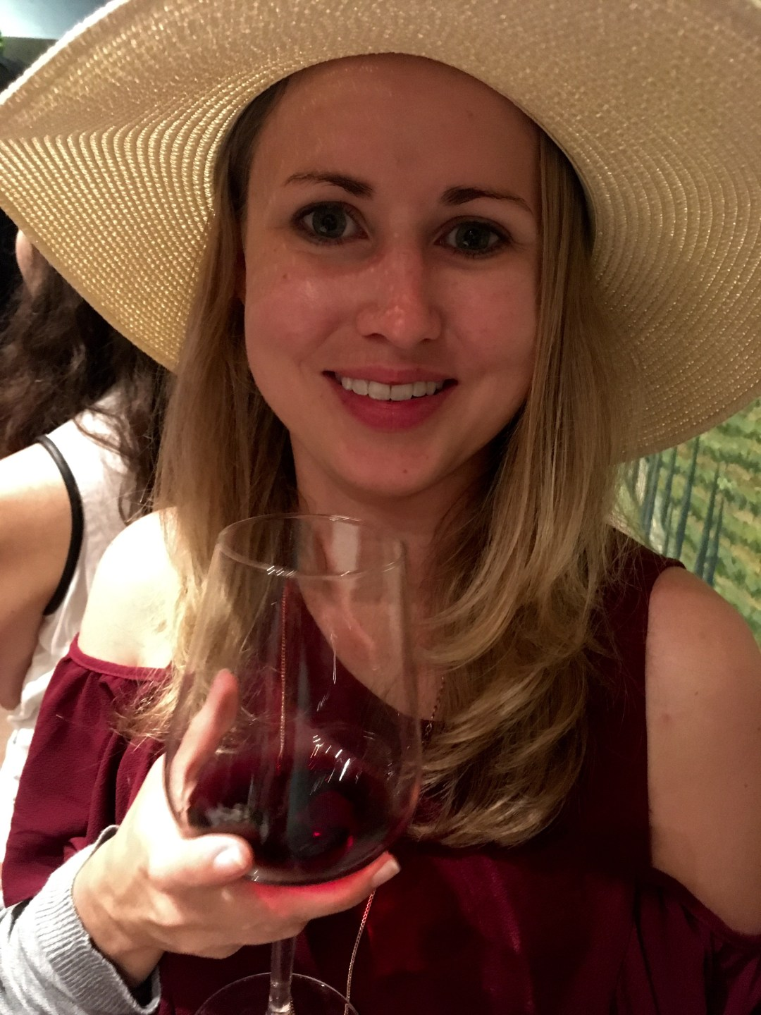 girl holding glass of Chianti red wine during wine tasting tour in Tuscany, Italy