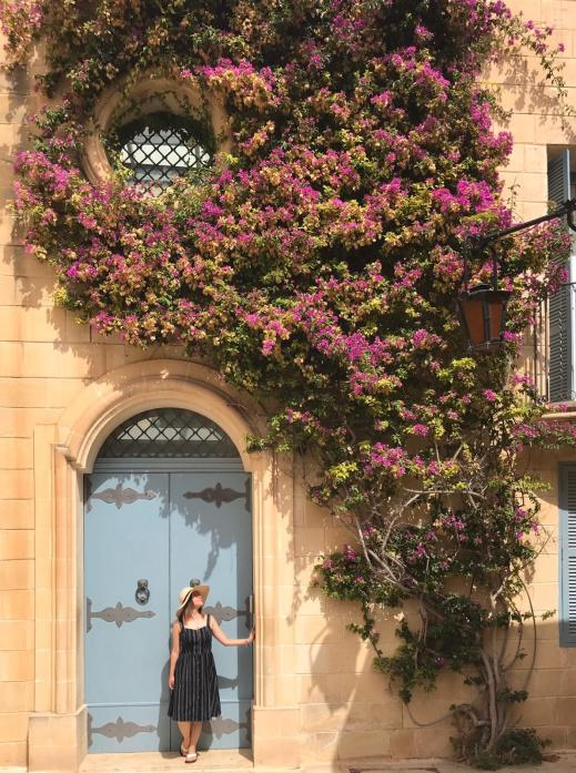 posing next to blue door framed by large flowing purple tree in Mdina, Malta