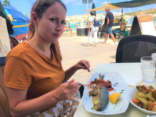 Girl eating lampuki fish in Marsaxlokk, Malta