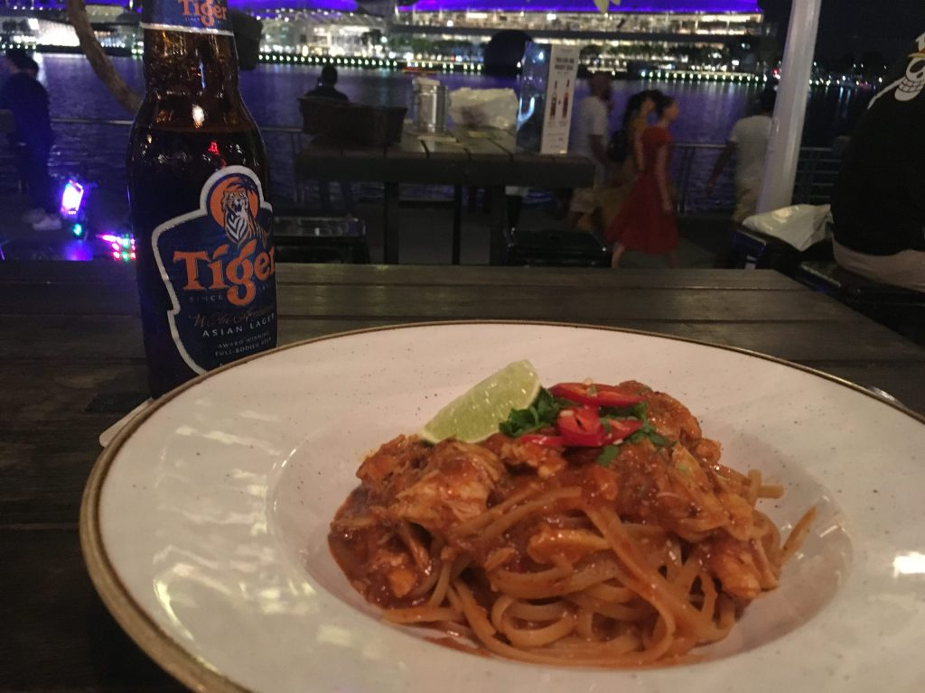 Chilli crab linguine and Tiger beer at restaurant near Marina in Singapore