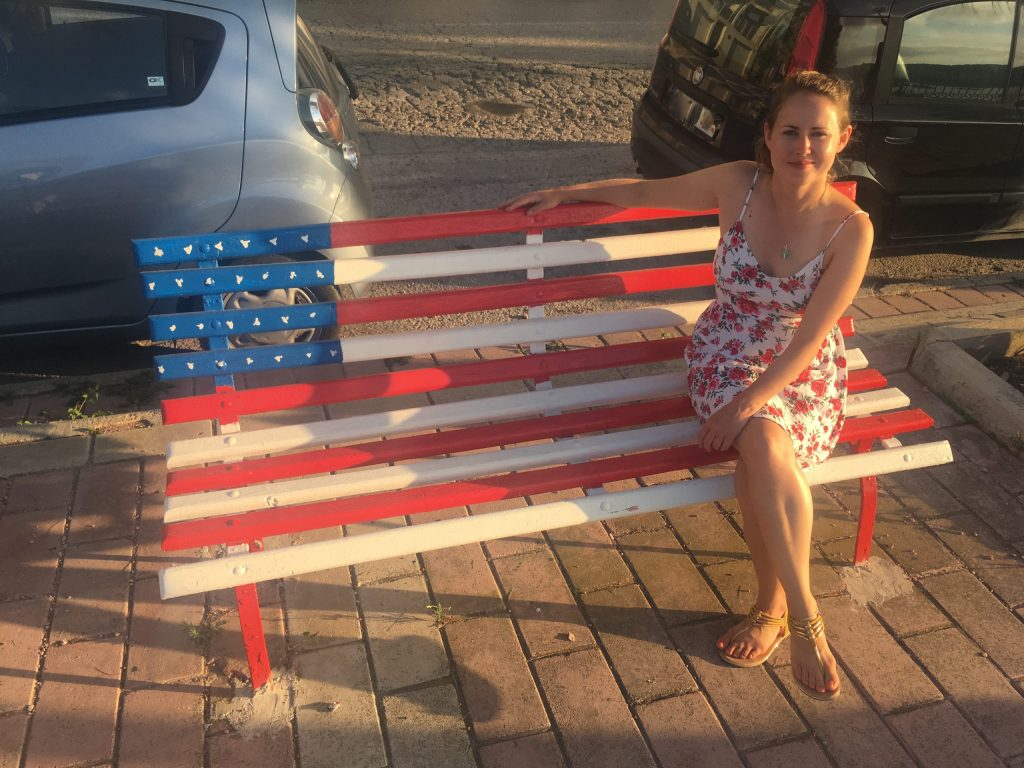 Girl sits on American flag painted bench in Malta