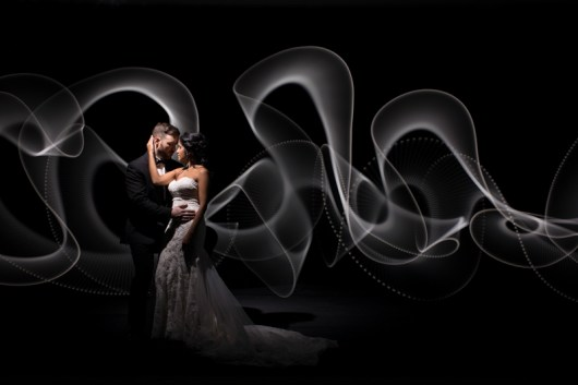A groom holding his bride during a photo with light painting behind them.