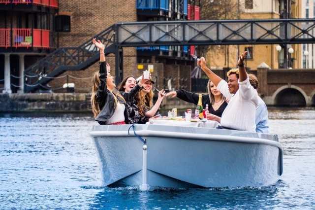 Un gruppo di amici saluta da una GoBoat in un viaggio intorno a Canary Wharf.