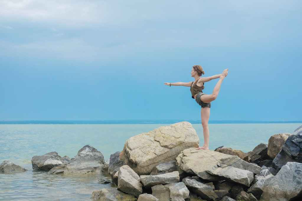 flexible woman performing yoga on coast of ocean