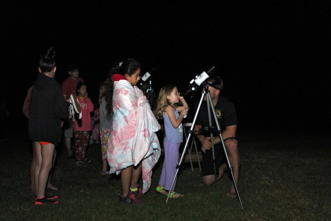 Kids use a telescope at Camp Einstein