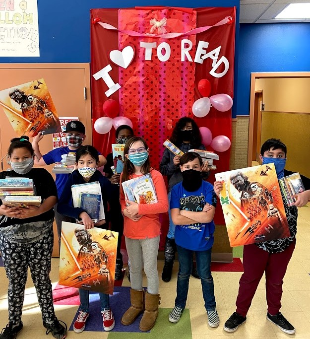 Kids hold their new books