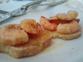 Scampi con arancia su crostini, shrimp cooked in an orange sauce on toast