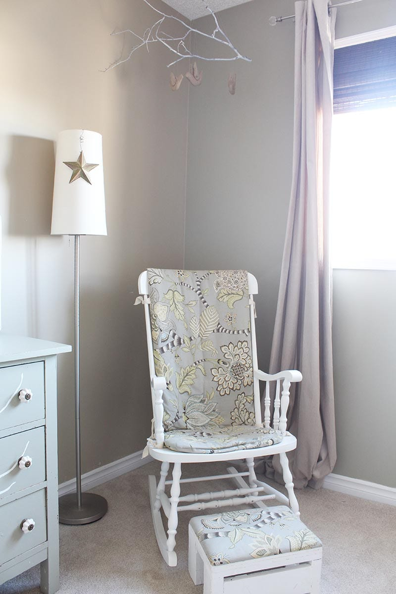 DIY tree branch mobile in a green and beige baby bedroom.