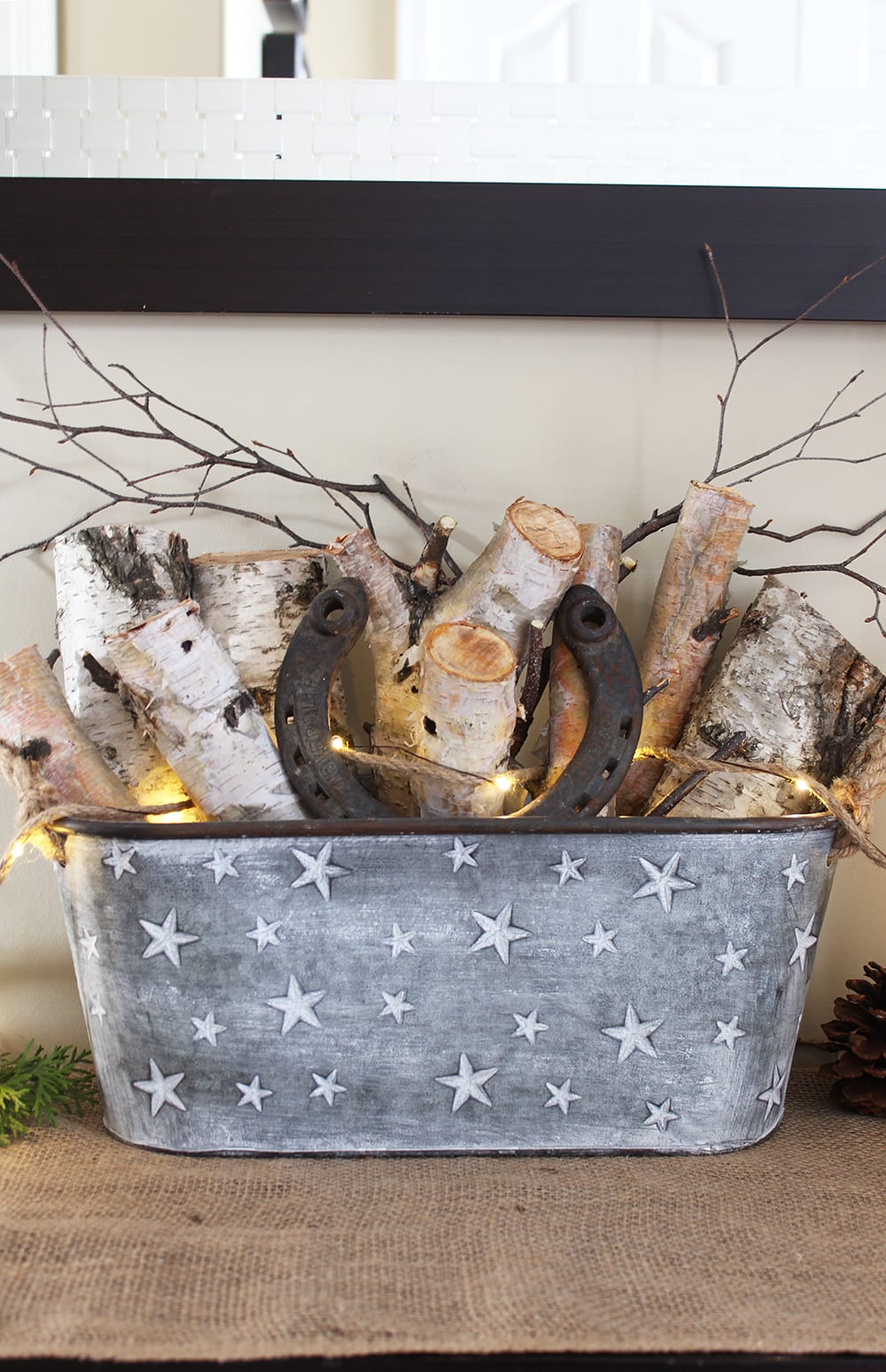 Nature inspired holiday decor featuring birch logs and twigs in a galvanized steel bucket, plus a horseshoe for good luck.