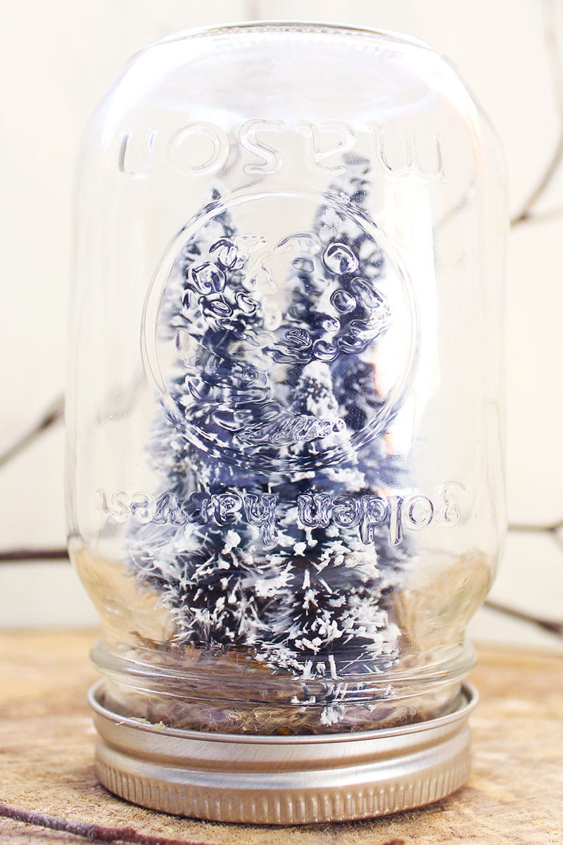 "A ""snow"" globe made from a reused mason jar, faux trees and burlap. A great addition to your winter craft ideas Pinterest board!"