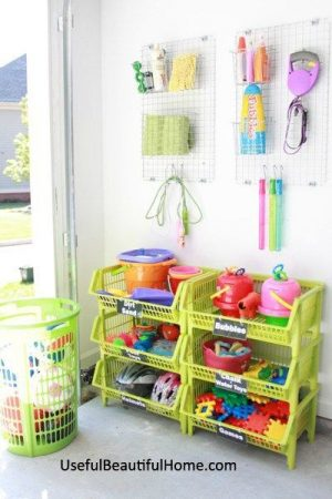 Organize kid toys in your garage using bright, colorful stackable bins. I love the green!