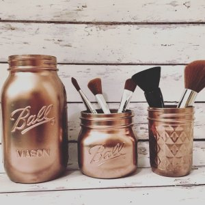 Spray paint mason jars for makeup brush storage and organization.