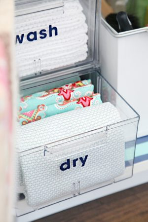 Use clear plastic containers to store your dish towels under the sink.