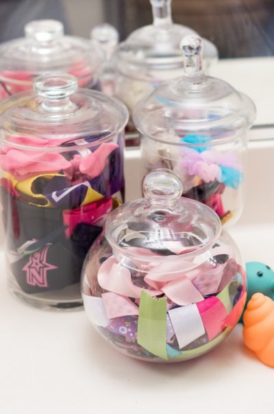 Use small candy jars and canisters to store and organize hair accessories and toiletries in the bathroom.