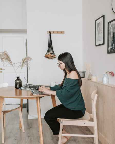 female remote worker typing on laptop at home