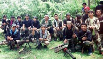 Abu Sayyaf leaders Khaddafi Janjalani, 2nd from left in front row, and Radulan Sahiron, 2nd from right in front row with headband, sit with fellow Abu Sayyaf rebels inside their jungle hideout somewhere in the area of Sulu province in the southern Philippines on Sunday July 16, 2000. It was the first time Janjalani allowed a photograph since they fled to Sulu from nearby Basilan island following their kidnapping of more than 50 people most of whom were school children. (AP Photo/STR)