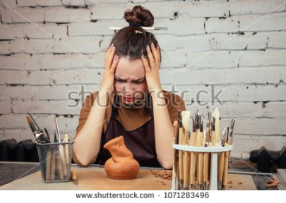 stock-photo-the-concept-of-sadness-and-lack-of-ideas-in-creativity-a-young-and-sad-woman-looks-at-a-vase-of-1071283496
