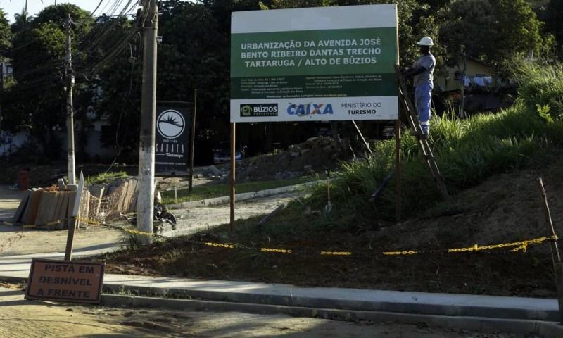 Em Búzios, operário recoloca no lugar placa anunciando obra que deveria estar concluída em fevereiro deste ano, na Avenida José Bento Ribeiro Dantas, principal acesso à cidade Foto: Antonio Scorza / Agência O Globo
