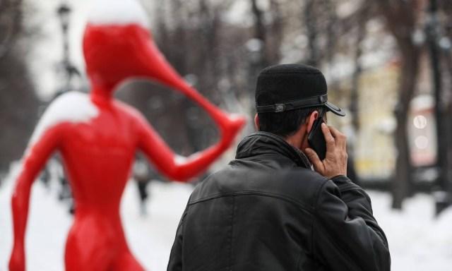 Um homem fala em seu telefone passando por um monumento de Mobile Web projetado por Yegor Shabanov em Petrovsky Boulevard Foto: Sergei Savostyanov / Sergei Savostyanov/TASS