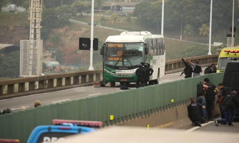 Sequestrador caído na escada do ônibus, após disparos Foto: Fabiano Rocha / Agência O Globo