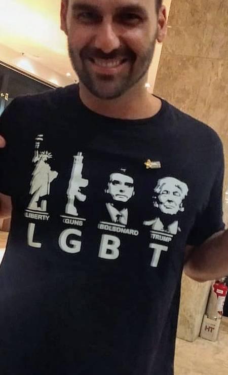 O deputado Eduardo Bolsonaro com uma camisa cuja estampa zomba da sigla LGBT, usando as cartas para exaltar os Estados Unidos, sua política armamentista, o presidente Jair Bolsonaro e o presidente americano Donald Trump