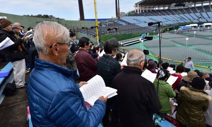 O sobrevivente da bomba atômica Kenji Hayashida, de azul, participa de um ensaio de canto no estádio de beisebol de Nagasaki, onde o Papa Francisco fará uma missa Foto: KAZUHIRO NOGI / AFP