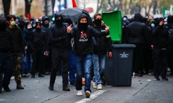 Um manifestante gesticula durante um protesto em Paris.  A manifestação começou com milhares de pessoas marchando pacificamente pela capital, com faixas que diziam
