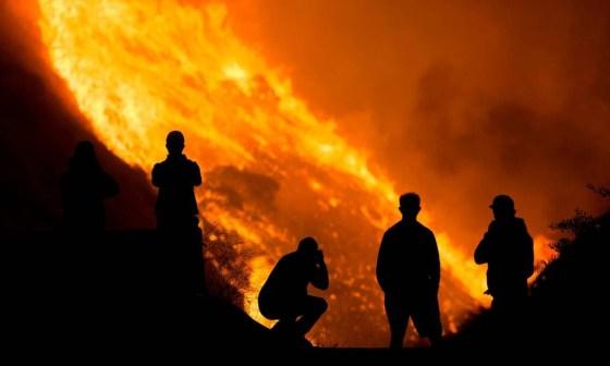 Moradores observam incêndio em casa em Yorba Linda, Califórnia: mudanças climáticas causarão mais secas e ondas de calor Foto: Ringo Chiu / REUTERS / 6-10-2020