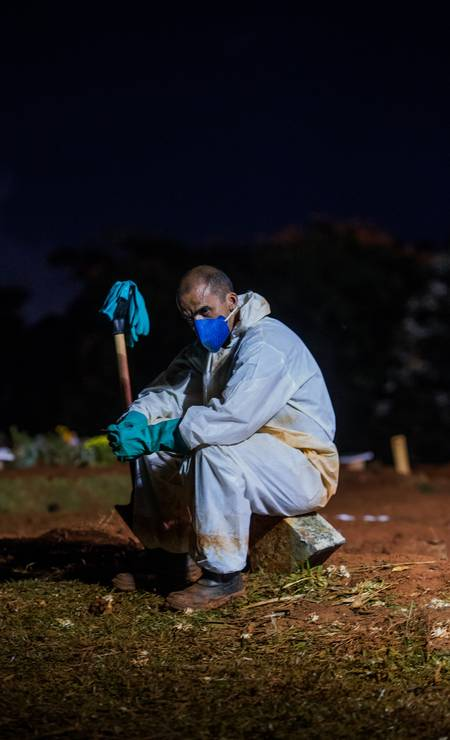 Coveiro wearing PPE against Covid-19 rests during night shift at Vila Formosa cemetery Photo: Edilson Dantas / Agência O Globo