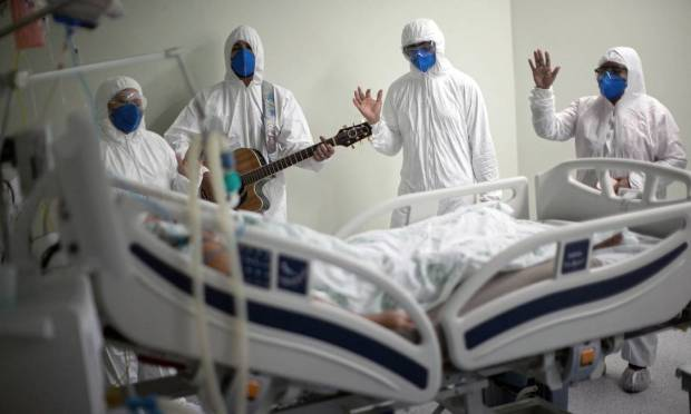 A team from the Portuguese charity hospital in Belém, Pará, sings to a patient with Covid-19 in a hospital bed Photo: TARSO SARRAF / AFP - 04/04/2021