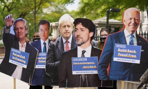 Manifestantantes em Washington usam cartazes com fotos de líderes que partiparão da cúpula para pedir medidas contra as mudanças climáticas Foto: KEVIN LAMARQUE / REUTERS