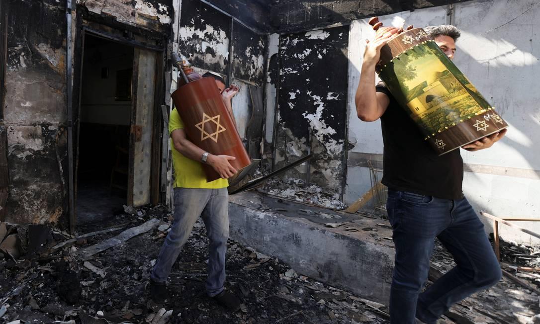 Rolos da Torá, escrituras sagradas judaicas, são removidos de uma sinagoga que foi incendiada durante confrontos violentos na cidade de Lod, em Israel, entre manifestantes árabes israelenses e a polícia Foto: RONEN ZVULUN / REUTERS