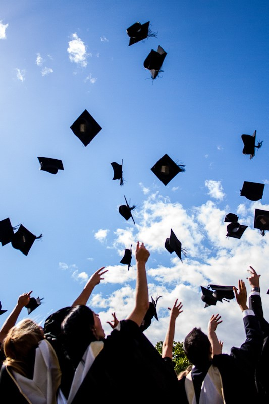 Graduation caps being thrown into a blue sky