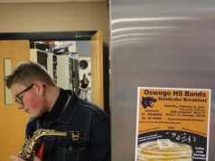 An OHS Saxaphone player practices his fingering next to a flyer for the Bandcake Breakfast.