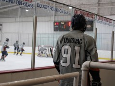 Junior Max Dakovac waiting to go on the ice during a hockey game
