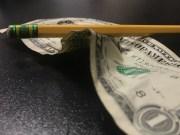 Crumpled dollar bill and pencil.