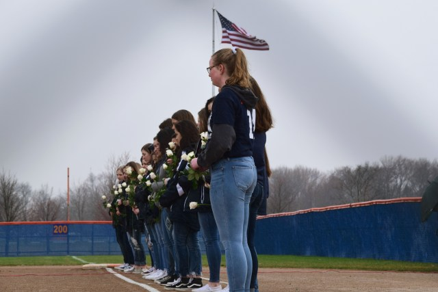 Softball players standing in a line with white roses