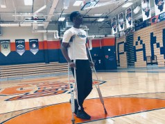 Reggie Townsend on crutches on the basketball court