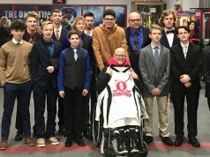 Oswego hockey team presents Mrs. Avalos with a jersey prior to their game
